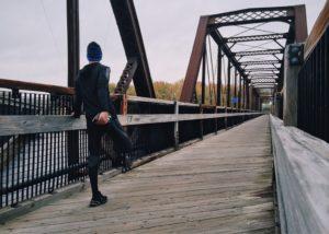 Mann steching an einer Brücke