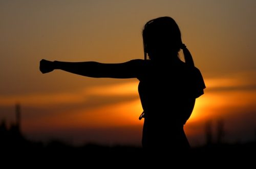 frau trainiert karate im sonnenuntergang